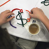 "Record-Eagle/Jan-Michael Stump<br /> Mary Kay Ash team member Mitchell Mosley of Traverse City Central High School uses pipe cleaners to design a logo for the group's company during Wednesday's Junior Achievement of Northwest Michigan Youth Summit for Entrepreneurs. 70 students from 15 high schools in six counties attended the event at the Hagerty Center in Northwestern Michigan College's Great Lakes Campus, where, in groups, they were challenged to repurpose a current item of their choice and develop business and marketing plans to present to judges. The winning team each received a ""money tree"" with $100 on it. Groups were named for famous entrepreneurs such as the cosmetics giant Ash."
