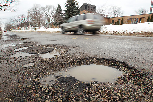Record-Eagle/Keith King<br /> A vehicle travels past potholes Monday, February 25, 2013 on Union Street in Traverse City.