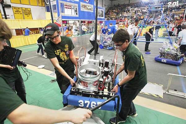 Record-Eagle/Keith King<br /> Patrick Schuster, left, and Charlie Rogers, of the Traverse City West High School Toxic Bots robotics team, lift their team's robot onto a cart to take it to the pit area Friday, March 1, 2013 during the FIRST (For Inspiration and Recognition of Science and Technology) in Michigan district robotics competition at Traverse City Central High School. The competition continues Saturday.