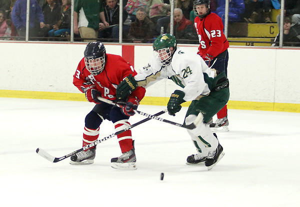 Record-Eagle/Keith King<br /> The Bay Reps' Mark Mol (13), left, and Traverse City West's Jacob Benker (24), go for the puck Tuesday, February 26, 2013 in Howe Arena at the Grand Traverse County Civic Center in Traverse City.