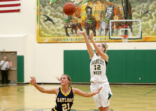 Record-Eagle/Keith King<br /> Traverse City West's Kiley Kreple (12) shoots a three-point shot and makes it against Gaylord's Sarah Polena (21) in the closing seconds of the fourth quarter to send the game into overtime Friday, March 1, 2013 at Traverse City West High School.