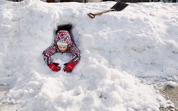 Record-Eagle/Jan-Michael Stump<br /> Magdalen Kleinrichert, 7, digs in a pile of snow on 15th Street while playing outside with her brother, Fletcher, 3, and grandpa, Roger Hendrickson, on Wednesday afternoon. There is a chance of more snow tonight and Friday.