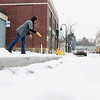 "Record-Eagle/Jan-Michael Stump<br /> Tammy Simerson shovels a wintry mix of ice and snow outside her store, The Red Dresser, on Hall Street on Friday morning. ""It's Northern Michigan, it's not spring yet, no way,"" said Simerson."