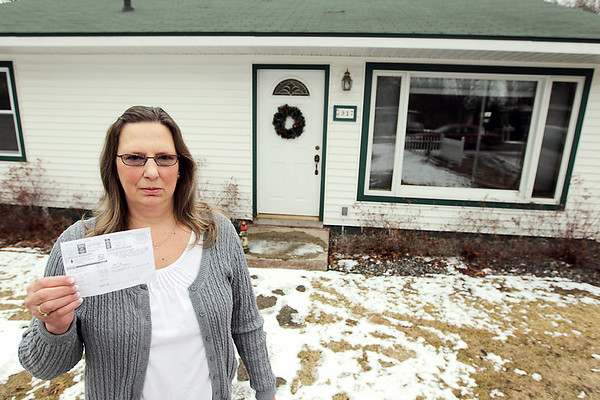 Record-Eagle/Keith King<br /> Rhonda Randall, of Traverse City, holds a  water and sewer bill for more than $7,800 at her East Bay Township home.