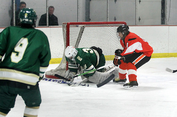 Record-Eagle/Keith King<br /> Traverse City West goalie, Michael Tilford, covers up the puck against Rockford's Zachary Vandawater Thursday, March 3, 2011 in Howe Arena at the Grand Traverse County Civic Center.