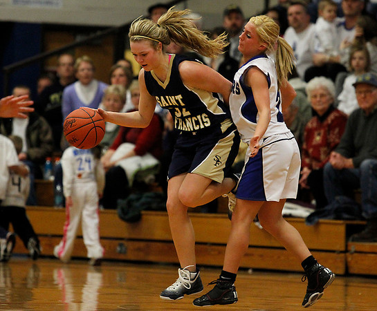 Record-Eagle/Jan-Michael Stump<br /> Traverse City St. Francis' Liza Erickson drives past Kalkaska's Chelsea Matley in the second quarter .