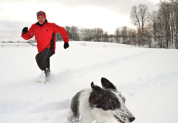 Record-Eagle/Allison Batdorff<br /> Maddie the Border collie uses boundless energy to get through the waist-deep snow; Kevin Deyo uses snowshoes. Deyo, 55, runs in his snowshoes four times a week in Twin Lakes Park.