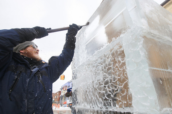Record-Eagle/Keith King<br /> Ryan Roth, sculptor, uses a chisel to create design on the fire and ice tower, created by Ice Creations, on Front Street during the Traverse City Winter Comedy Arts Festival.