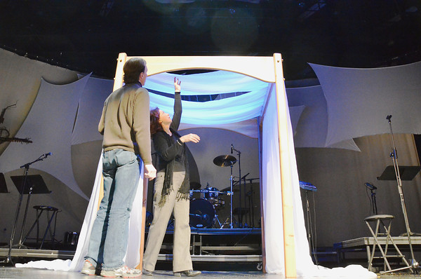 """Record-Eagle/Allison Batdorff<br /> Bay Pointe Community Church staffers Linda Lewis, right, and Chris Bornschein, left, prepare the """"huppa"""" for the next installment in the series """"Marriage: Why Bother?"""" The """"huppa,"""" a traditional Jewish wedding canopy, is an apt symbol for the series as couples who enter it must """"submit"""" to God first and foremost, Lewis said. Modern marriage tends to be over-idealized or undervalued, she said."""