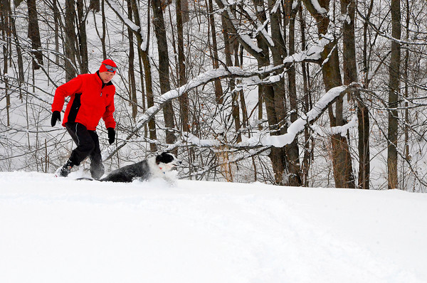 Record-Eagle photos/Allison Batdorff<br /> This season's snowy weather makes for robust snowshoe sales, rentals and a great workout. Traverse City snowshoe racer Kevin Deyo directly mounts his sneakers to his snowshoes and runs with his dog, Maddie.