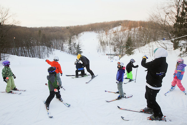 Record-Eagle/Keith King<br /> Students and instructors with a Grand Traverse Ski Club clinic gather at the top of a hill Friday at Hickory Hills Ski Area in Traverse City.