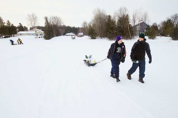 Record-Eagle/Keith King<br /> Nick Hains, left, 13, and Thomas Pettinato, 13, both of Traverse City, walk on Cedar Lake to participate in the Elmwood Township Sesquicentennial Kids Ice Fishing Tournament with the tournament put on by Elmwood Township and the Grand Traverse Area Sport Fishing Association.