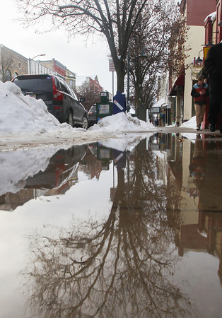 Record-Eagle/Keith King<br /> A tree is reflected in a puddle along Front Street as Jon DeGroote, of Lake Ann, walks past in above-freezing temperatures.