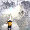 Special to the Record-Eagle/Tom Auch<br /> George Meredith stands in the mouth of a massive ice cave on Lake Michigan north of Leland on Feb. 11. Tom Auch, an instructor at Northwestern Michigan College was one of the first people to hike the 1/3 mile out onto the ice to find the caverns.