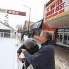 Record-Eagle/Keith King<br /> Mike Collins, left, and Marty Pavlock, volunteers, hang lights from the ice-skating rink on Front Street Friday for the Traverse City Winter Comedy Arts Festival.
