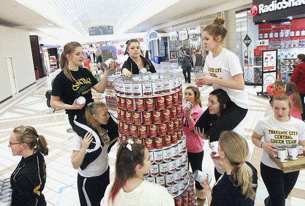 Record-Eagle/Keith King<br /> Teammates on the Traverse City Central High School varsity cheer team work together to make a lighthouse out of cans at the Grand Traverse Mall Saturday, February 2, 2013 during the 2nd annual Canstruction-TC competition to benefit the Father Fred Foundation food pantry. The sculptures built by teams, who worked with area architects that donated their time and expertise, are scheduled to be on display through February 7 at the Grand Traverse Mall.