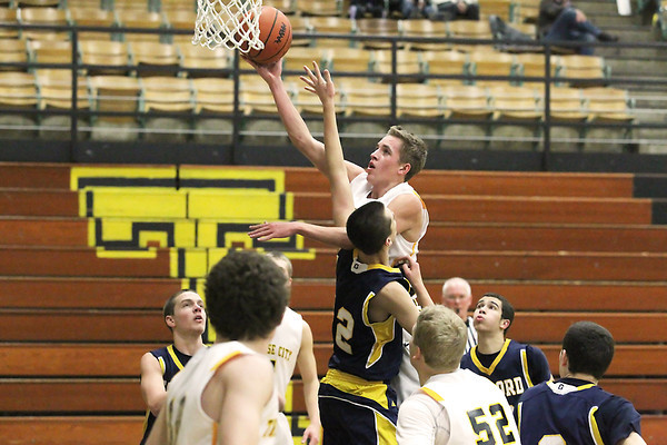 Record-Eagle/Jan-Michael Stump<br /> Traverse City Central's Ethan Pilarsk (20) shoots over Gayord's Tyler Cherry (2) in the second quarter of Tuesday's game.