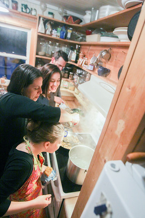 Record-Eagle/Keith King<br /> Sonja Daniels Moehle, from bottom, 9, Amy Daniels Moehle, Nadia Daniels Moehle, 13 and David Moehle, of Beulah, prepare dinner in their kitchen.