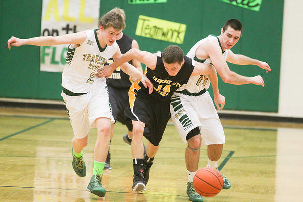 Record-Eagle/Keith King<br /> Traverse City West's KJ Sayer (2), from left, Traverse City Central's Nate Schlusler (14) and Traverse City West's Ty Troxell (14), right, battle for possession of the ball Thursday at Traverse City West High School.