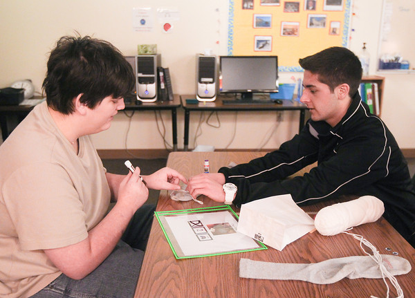 Record-Eagle/Keith King<br /> Chris Bowden, left, a Traverse Bay Area Intermediate School District (TBAISD) student with autism, along with Logan Hisem, a Traverse City West High School student, work on making a puppet Thursday during the Peer-to-Peer Mentoring Program for Students with Autism, at Traverse City West High School. The puppets are planned to be used for an upcoming skit as part of the program.
