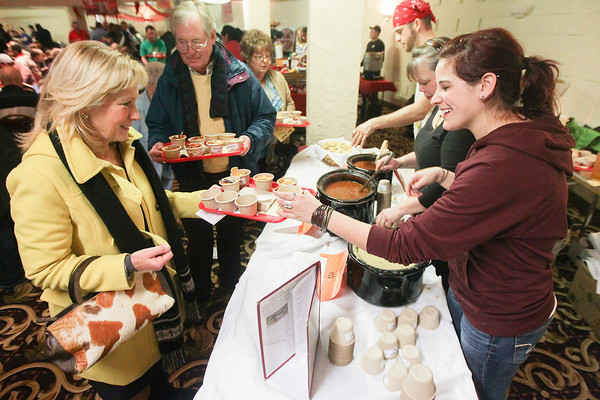 Record-Eagle/Keith King<br /> Tuck Maxwell, from left, and Tom Cowell, both of Traverse City, receive chili as Nathan Sigsbey, Nancy Freund (who's family has owned Little Bohemia for 45 years) and C.C. Burgess, far right, serve chili Saturday during the 20th annual Downtown Chili Cook-Off at the Park Place Hotel Dome in Traverse City. Proceeds from the event go to Downtown Traverse City Association community events such as Friday Night Live.
