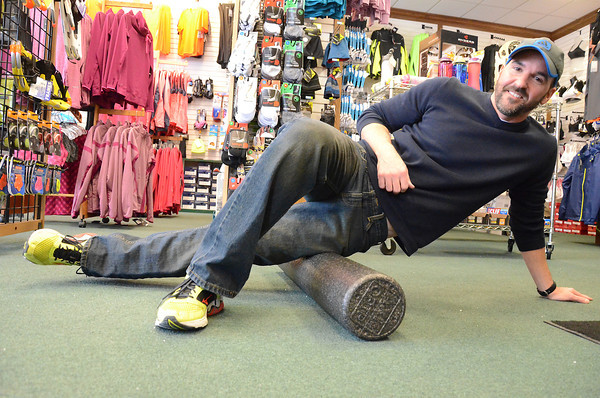 """Record Eagle Photo/Allison Batdorff<br /> Marc McCombs demonstrates foam rolling — a concept based on using body weight to roll out the fascia (or connective tissue beneath the skin) like cookie dough to break up knots and increase blood flow around the body.  The Traverse City-based personal trainer has seen this fitness practice """"explode"""" in popularity in recent years and sells them every day in his job at Running Fit."""