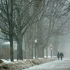 Record-Eagle/Jan-Michael Stump<br /> A couple walks down Seventh Street as snow returns to Traverse City.