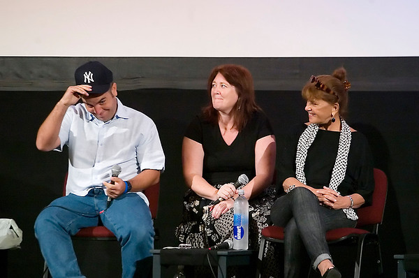 "Record-Eagle/Jan-Michael Stump<br /> Cuban director Ian Padron puts on a New York Yankees hat as interpreter Bryn Lynch, center, and actress Mirta Ibarra watch during Friday's ""We Live in Cuba and We Make Movies"" panel at the City Opera House."