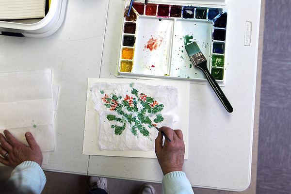 Record-Eagle/Jan-Michael Stump<br /> Marie Cornell  paints using a technique involving tissue paper during Traverse City artist Charles Murphy's weekly watercolor class Wednesday at the Traverse City Senior Center.