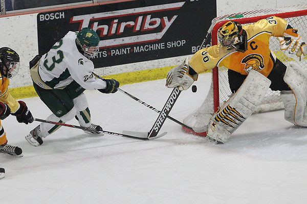 Record-Eagle/Jan-Michael Stump<br /> Traverse City Central goalie Bill Vermetten (30) stops Traverse City West's Nick Schultz (23) while Central's Brady Brantley (2) defends Wednesday at Howe Arena.