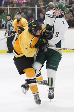 Record-Eagle/Jan-Michael Stump<br /> Traverse City Central's Cooper Macdonell (7) and Traverse City West's Dan Henderson (8) collide near center ice in the third period Wednesday at Howe Arena.