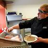 Record-Eagle/Jan-Michael Stump<br /> Soul Hole chef Scott Williams prepares a pork butt with a mesquite rub before smoking it for his Texas Tornado chili.