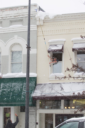 Record-Eagle/Keith King<br /> Bob Walters, top, of Traverse City, using direction from Pierre Pujos, bottom left, utilizes an extension pole to remove snow from the cornice of the building which houses Pavlova European Salon and Day Spa, which Pujos owns, in downtown Traverse City.
