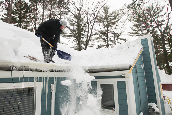 Record-Eagle/Keith King<br /> Dave Andersen, with Grand Traverse Roofing, shovels snow off the roof of a home in East Bay Township.