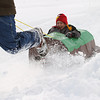 Record-Eagle/Jan-Michael Stump<br /> Cole Steffes of Cub Scout Pack 87 from Silver Lake Elementary, rides in his sled made entirely from cardboard and duct tape, as his father Larry Steffs pulls him during Saturday's 8th Annual Cub Scout Pack Winter Wonders Sled Outing Saturday at West Side Community Church near Traverse City. The event hosted about 15 packs from the Bay Trails District of the President Gerald R. Ford Field Service Council, which includes Leelanau, Grand Traverse and Kalkaska Counties, featured snowmobile rides, sled races and a cardboard/duct tape sled contest.