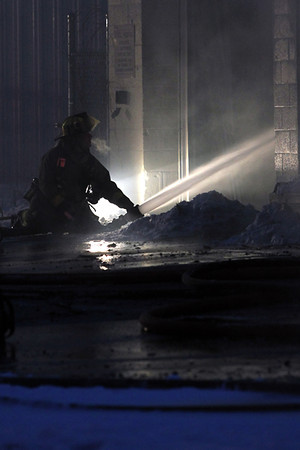 Record-Eagle/Jan-Michael Stump<br /> A Traverse City Fire Fighter sprays water on a fire at Arrow Roofing and Supply, Inc. on Wellington Street, just south of East Eighth Street in Traverse City on Monday afternoon.