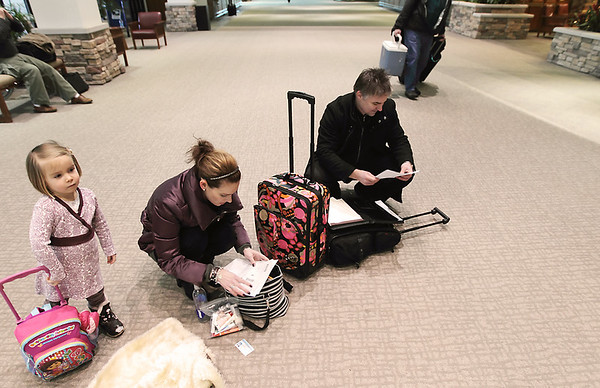 Record-Eagle/Keith King<br /> Gary Ruoff, right, of Traverse City, and his wife Susan Ruoff organize their bags while retrieving identification cards and travel information as their daughter Lola Ruoff, 3, stands nearby prior to departing from the airport.