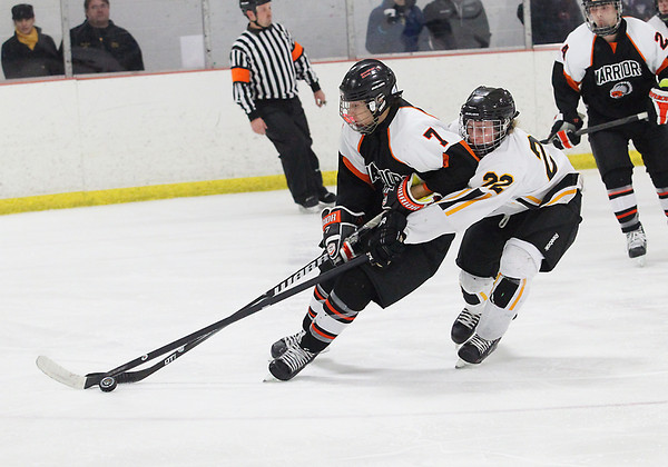 Record-Eagle/Jan-Michael Stump<br /> Brother Rice's Russell Cicerone (7) skates past Traverse City Central's Jon Russell (22) in the second period of Friday's game.