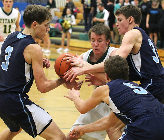 Record-Eagle/Jan-Michael Stump<br /> Petoskey's Erik Davenport (3), Sam Baumgartner (5) and Louie Lamberti (34) fight for the ball with Traverse City West's Jeremish Williams (12) in the second half of Tuesday's game.