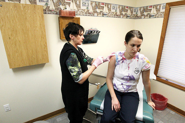 Record-Eagle/Keith King<br /> Donna Rinker, board certified family nurse practitioner, gives a flu shot to Amber Darin, of Williamsburg, Friday, January 11, 2013 at Bayside Docs Urgent Care facility in Traverse City.