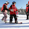 Record-Eagle/Keith King<br /> Aaron O'Brien, of Traverse City, aided by Adrienne Jones, left, of Frankfort, snowboards at Crystal Mountain Resort on Saturday during a Northern Michigan Adaptive Sports and Recreation ski and snowboard session.