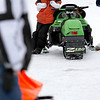"Record-Eagle/Jan-Michael Stump<br /> Rocky Rasho, 8, of Interlochen, watches other racers take practice laps during Friday's qualifying for Saturday's TC 250 Vintage Snowmobile One Lunger Race in Interlochen. Rasho was born with ulnar mammary syndrome, a genetic birth disorder that results in abnormalities of the hands and forearms, and has to use socks to keep warm. ""We can't find gloves or mittens to fit him,"" said his mother, Sarah Miner. Rasho won last year's race in the kitty cat division and will be competing in the 120 division this year."