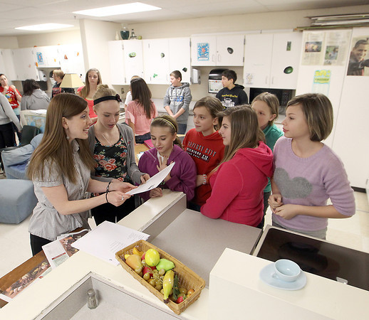 Record-Eagle/Jan-Michael Stump<br /> Traverse City West Middle School global foods teacher Rebecca Walters goes over a recipe for tres leche cake with, from left, Anja Ignace, Breleigh Welch, Lauren Jacobs, Hanna Giurlanda, Brianna Rickert and Avery Kostrzewa in class Tuesday.