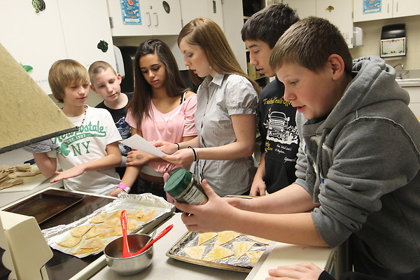 Record-Eagle/Jan-Michael Stump<br /> Traverse City West Middle School global foods teacher Rebecca Walters, third from right, goes over a recipe for parmesan garlic  tortilla chips with, from left, Damon Nelson, Gary Hlavka, Aliesha Bockhol, Guillermo Yarmuth and Ty Ebling  in class Tuesday.