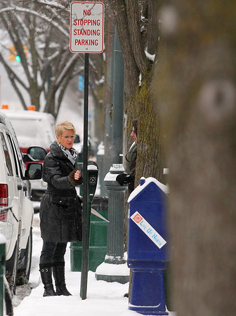 Record-Eagle/Jan-Michael Stump<br /> Rita Whaley puts change in a Front Street parking meter on Thursday morning. Traverse City is going to start allowing people to pay parking meters using their cell phones.