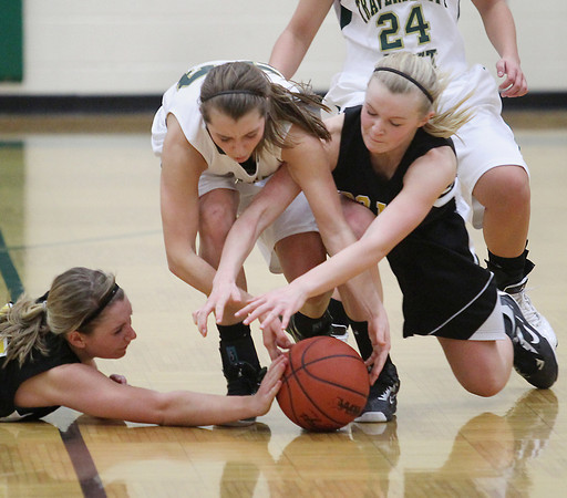 Record-Eagle/Keith King<br /> Traverse City Central's Madi Bankey (14), left, Taylor Cobb, right, and Traverse City West's Kimmy Bilinski, middle, battle for possession of the ball Friday, January 18, 2013 at Traverse City West High School.