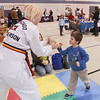 Record-Eagle/Keith King<br /> Jennifer Anderson, with the Traverse City American Taekwondo Association (ATA) Martial Arts, holds a board as Ethan Novak, 4, of Traverse City, prepares to break the board as Anderson conducts a board-breaking lesson Saturday during the 2014 Grand Traverse Area Preschool and Child Resource Fair at Trinity Lutheran School in Traverse City.