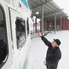 Record-Eagle/Keith King<br /> John Wicksall, Bay Area Transportation Authority driver, brushes snow from the back of his bus at the transfer station on Hall Street in Traverse City.