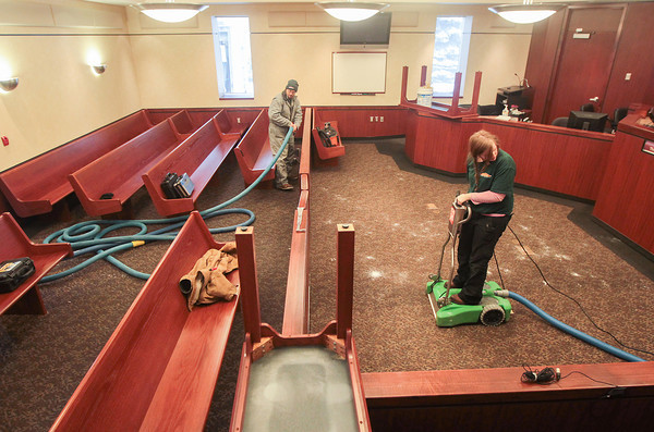 Record-Eagle/Keith King<br /> Daniel Priem, left, and Mary Randall, both with SERVPRO of Grand Traverse Area, use machines to extract water after a pipe broke and leaked water into courtroom one in 86th District Court at the Robert P. Griffin Hall of Justice in Traverse City.