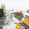 Record-Eagle/Keith King<br /> John Fall, left, and Adam Adamczak, with the City of Traverse City Parks and Recreation Department, put trees into a chipper Tuesday at Hull Park in Traverse City at the Christmas tree drop-off area. Trees, wreaths and garland, which shouldn't have anything on them such as wires, lights or nails, can be dropped off at the site where they'll be chipped with the chips planned for use on area trails for landscaping, maintenance and erosion control. The site is scheduled to be open for drop-off through Sunday, January 19.